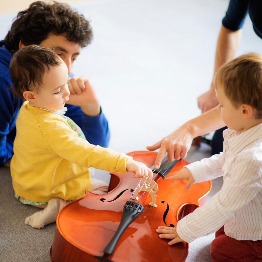 Jeunes enfants touchant un violoncelle sous la supervision d'un adulte